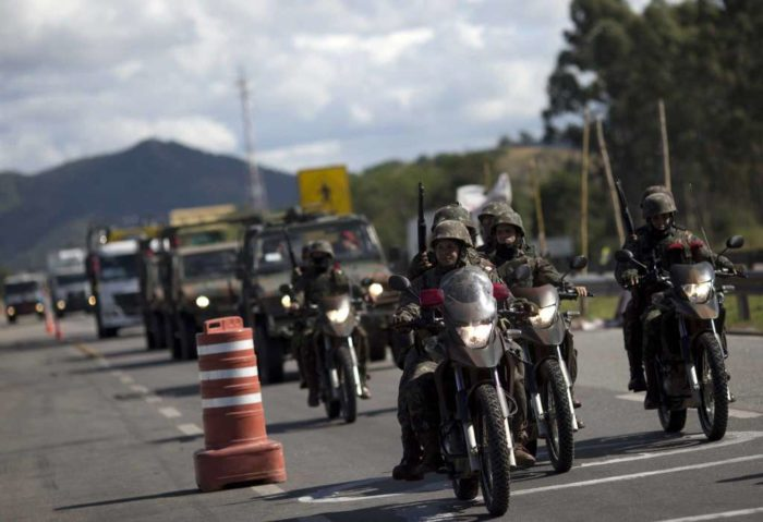 Soldiers escort truckers who have stopped striking on Highway BR-116, in Rio de Janeiro, Brazil, Tuesday, May 29, 2018. Brazilian truckers frustrated by rising fuel prices are striking for a ninth day in several states, though sporadic deliveries of gasoline and goods are starting to ease a shutdown that has led to widespread shortages and disturbances. Photo Credit: Silvia Izquierdo/AP