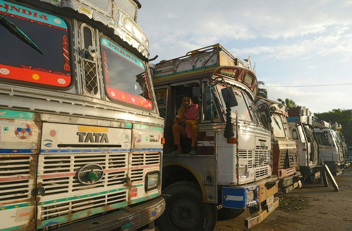 An Indian truck driver sits on his truck at Fulbari truck terminus, on the outskirts of Siliguri. July 26, 2018. - An indefinite strike the declared by All-India Motor Transport Congress started on July 20 and received support from various truck associations across the country in a bid to reduce prices for fuel, tolls and taxes amongst other demands. (Photo by DIPTENDU DUTTA / AFP)